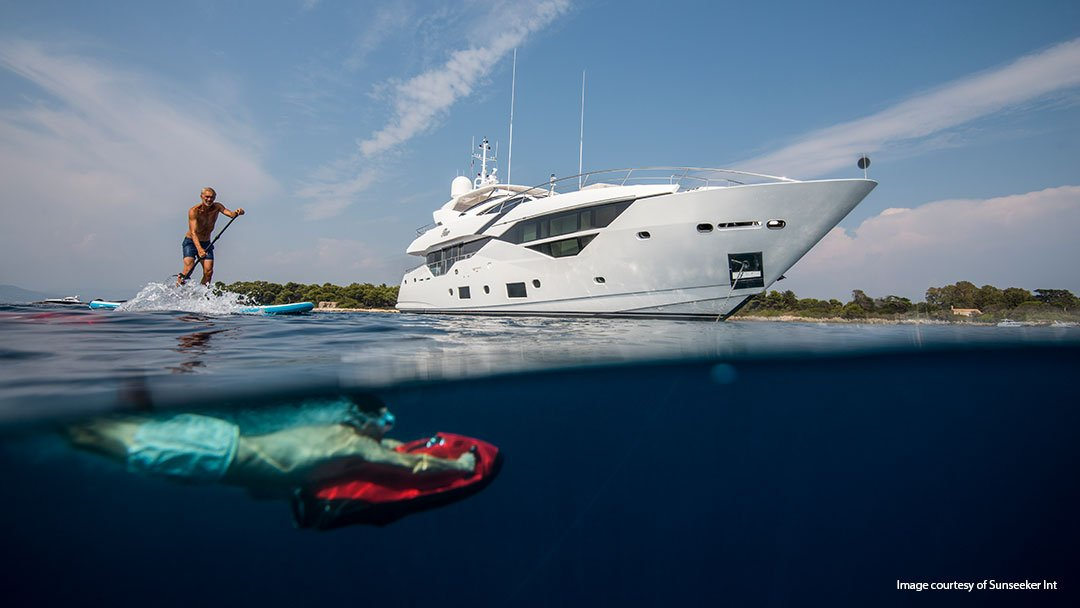 People playing in the water next to a sunseeker with vector fins stabilizers